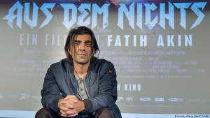 Director Fatih Akin in front of a poster for ″In the Fade″ (photo: dpa/picture-alliance)